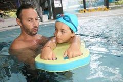 学会如何的小男孩游泳与显示器 库存照片