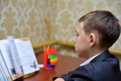 学会如何的小男孩选择聚焦在家写他的名字,孩子研究,孩子在家做家庭作业,小孩的概念 库存照片
