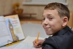 学会如何的小男孩选择聚焦在家写他的名字,孩子研究,孩子在家做家庭作业,小孩的概念 库存图片