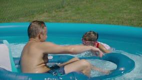 学会如何的愉快的小女孩游泳在水池 一起笑-慢动作的父亲和女儿 影视素材