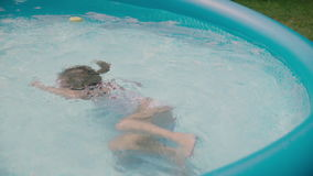 学会如何的愉快的小女孩游泳在水池 一起笑-慢动作的父亲和女儿 股票视频