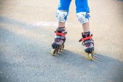 学会对溜冰鞋的小男孩在夏天公园 佩带安全滑旱冰乘驾的孩子保护垫 活跃室外 免版税库存照片