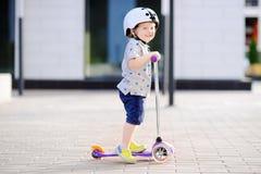 学会小孩的男孩乘坐滑行车 库存图片