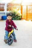 学会小小孩的男孩乘坐在他的第一辆自行车 免版税库存照片