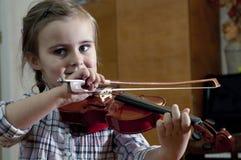 学会小提琴使用的可爱的小女孩 免版税库存照片