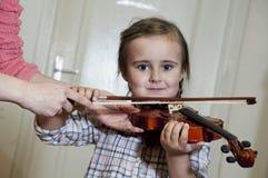 学会小提琴使用的逗人喜爱的学龄前女孩 库存照片