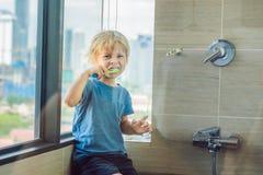 学会小白肤金发的男孩刷他的在国内浴的牙 学会如何的孩子停留健康 背景弄脏了关心概念表面健康防护屏蔽的药片 库存照片