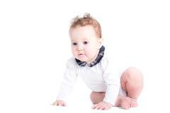 学会小的女婴爬行,隔绝在白色 库存图片