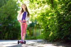 学会小的孩子乘坐一辆滑行车在城市公园在晴朗的夏天晚上 乘坐路辗的逗人喜爱的小女孩 免版税库存图片