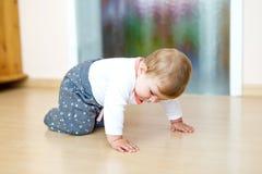 学会小逗人喜爱的女婴爬行 爬行在孩子屋子里的健康孩子 微笑的愉快的健康小孩女孩 逗人喜爱 免版税库存图片