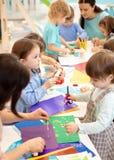 学会幼儿园的发展孩子 儿童的项目在幼儿园 切开纸的小组孩子和老师 免版税库存照片