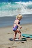 学会怎么的孩子对在拉古纳海滩的skimboard, C 免版税库存照片