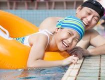 学会愉快的女孩游泳在与父亲的游泳池 免版税库存照片