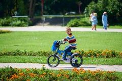 学会愉快的男孩骑他的第一辆自行车 图库摄影