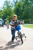 学会愉快的男孩骑他的第一辆自行车 免版税库存图片