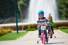 学会愉快的男孩骑他的第一辆自行车 免版税图库摄影