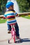 学会愉快的男孩骑他的第一辆自行车 免版税库存照片