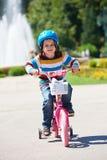 学会愉快的男孩骑他的第一辆自行车 库存图片