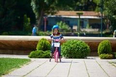 学会愉快的男孩骑他的第一辆自行车 库存照片