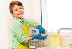 学会愉快的男孩洗盘子在厨房里 免版税库存照片