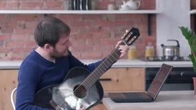 学会戏剧吉他的快乐的音乐家人使用有网上录影教学的手提电脑并且享受音乐 影视素材