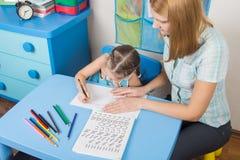 学会拼写的辅导者和五岁的孩子 免版税库存照片