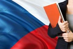 学会捷克语言概念 与捷克旗子的年轻女人身分在背景中 拿着书的老师, 库存图片