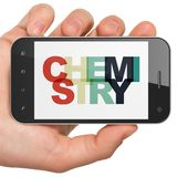 学会概念:拿着有化学的手智能手机在显示 免版税库存照片