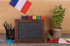 学会法语概念-空白的黑板,法国的旗子,书,铅笔,指南针 免版税库存图片