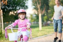 学会的女孩骑有父亲的一辆自行车在公园 免版税库存照片