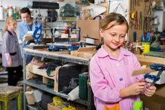 学会的女小学生雕刻木头在艺术和工艺期间分类 免版税图库摄影