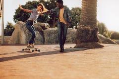 学会的妇女乘坐滑板 免版税库存照片