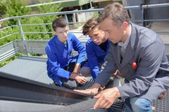 学会的学徒安装省能源的太阳电池板在屋顶 库存照片