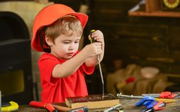 学会的孩子使用螺丝刀 在运作在车间的橙色盔甲的被集中的孩子 未来职业概念 库存照片