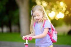 学会的小孩乘坐一辆滑行车在城市公园在晴朗的夏日 乘坐路辗的安全帽的逗人喜爱的学龄前儿童女孩 免版税库存图片