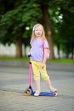 学会的小孩乘坐一辆滑行车在城市公园在晴朗的夏日 乘坐路辗的安全帽的逗人喜爱的学龄前儿童女孩 图库摄影