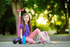 学会的小孩乘坐一辆滑行车在城市公园在晴朗的夏日 乘坐路辗的安全帽的逗人喜爱的学龄前儿童女孩 免版税库存照片