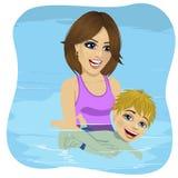 学会的小男孩游泳在游泳池,抱孩子的母亲 免版税库存图片