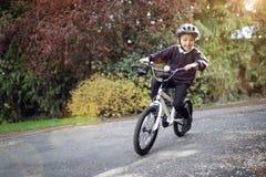 学会的男孩骑他的自行车 图库摄影