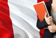 学会秘鲁语言概念 与秘鲁旗子的年轻女人身分在背景中 拿着书,橙色空白的老师 图库摄影