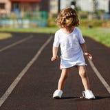 学会美丽的小女孩栓鞋带 库存图片