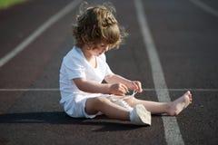 学会美丽的小女孩栓鞋带 免版税图库摄影