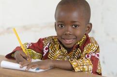 学会英俊的矮小的非洲黑人的男孩画象写 免版税库存照片