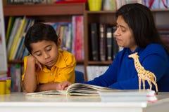 学会西班牙的孩子读与妈妈 免版税库存照片