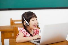 学会计算机的小女孩在教室 免版税库存照片