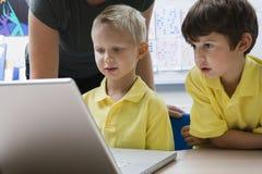 学会计算机科技的男小学生 免版税库存照片