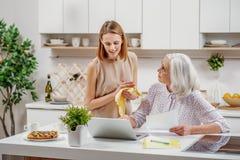 学会资深的母亲在厨房使用计算机 免版税库存图片