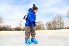 学会逗人喜爱的小男孩在冬天滑冰 图库摄影