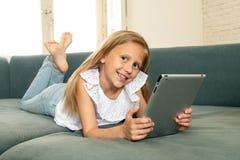 学会,使用和冲浪在有片剂的互联网上的愉快的逗人喜爱的孩子有巨大兴趣的 库存照片