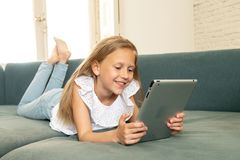 学会,使用和冲浪在有片剂的互联网上的愉快的逗人喜爱的孩子有巨大兴趣的 免版税库存图片